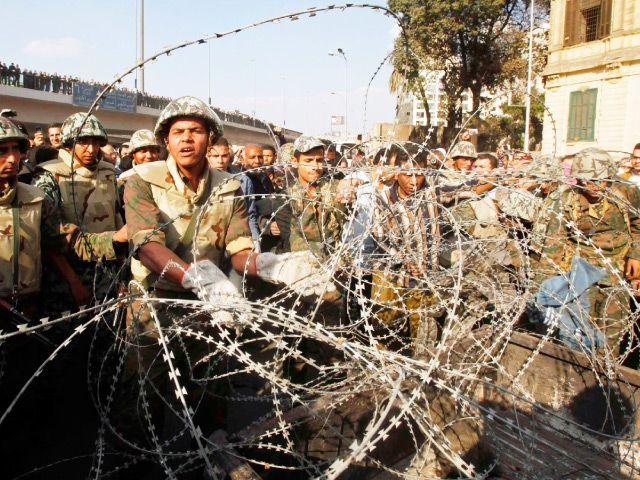 جنود مصريون يزيلون الأسلاك الشائكة على خط المواجهة قرب ميدان التحرير أمس(رويترز)