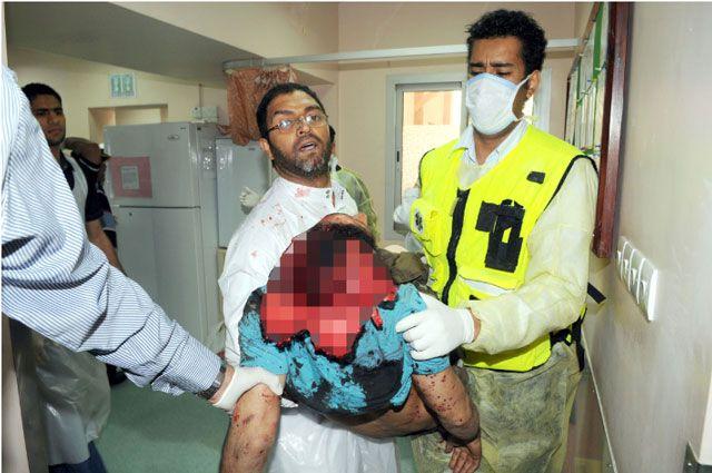 أحمد فرحان محمولاً من قبل الكادر الطبي بعد إعلان وفاته       وتمت تغطية  صورة الرأس لبشاعة المنظر       (تصوير: عيسى إبراهيم