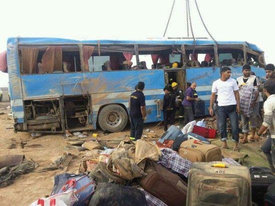 أمتعة ركاب الحافلة التي انقلبت متناثرة على الأرض فيما يظهر شباب يحيطون بالحافلة