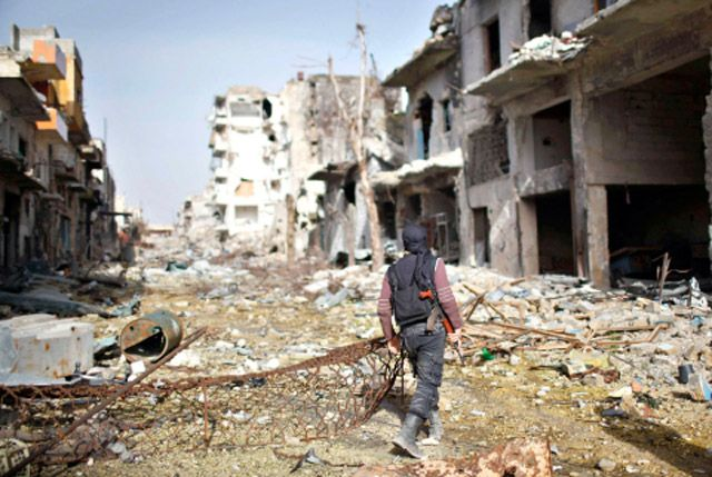 أحد المقاتلين الإسلاميين التابعين للمعارضة يسير في شوارع حلب المدمرة - REUTERS