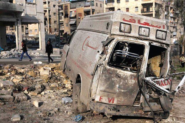 سكان يمرون قرب سيارة إسعاف مدمرة في حلب - REUTERS