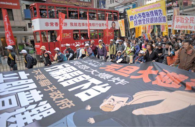 آلاف من داعمي الديمقراطية يتظاهرون للمطالب بتنحي الرئيس التنفيذي لهونغ كونغ - AFP