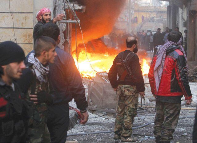 عناصر من «الجيش السوري الحر» يقفون قرب حريق خلفه قصف للقوات النظامية في حلب - REUTERS