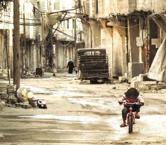 طفلة سورية تلهو بدراجتها في شارع شبه مهجور في حي تشرين بدمشق - afp