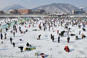 الآلاف يصطادون السمك من خلال ثقوب بنهر متجمد في كوريا الجنوبية بالمهرجان السنوي للصيد في الجليد - AFP