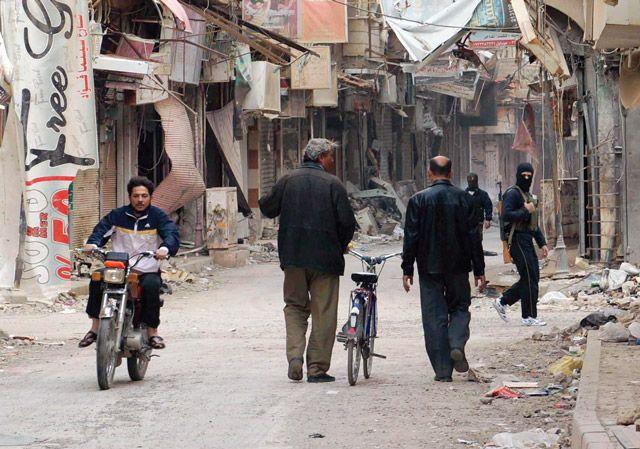 مواطنون سوريون يمرون بشارعٍ تمركز فيه أحد مقاتلي المعارضة في دير الزور - AFP