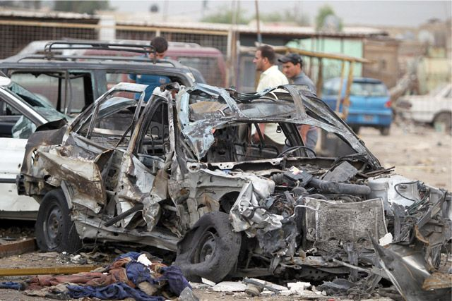 عراقي يمر خلف موقع تفجير انتحاري في مدينة الصدر - AFP