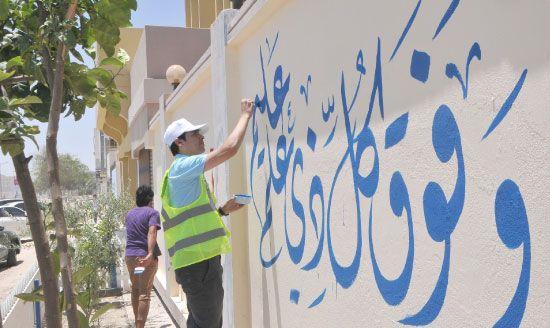 مشارك في فعالية ارتقاء يخط على أحد جدران القرية - تصوير عقيل الفردان