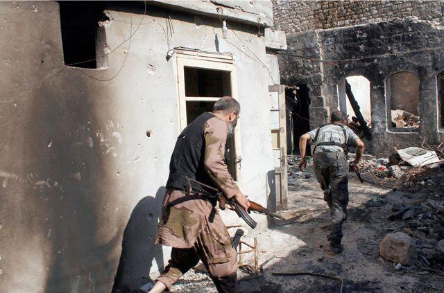 مقاتلون من «الجيش الحر» يركضون بحثاً عن غطاء أثناء اشتباكات في حلب  - REUTERS