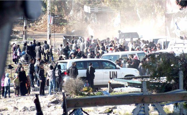مدنيون سوريون يستعدون  لإجلائهم من المنطقة المحاصرة من حمص - REUTERS