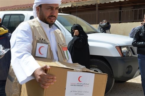 عضو من هيئة الهلال الأحمر الإماراتي يوزع مساعدات على اللاجئين السوريين في مدينة المفرق الحدودية شمال الأردن (مارس 2012)