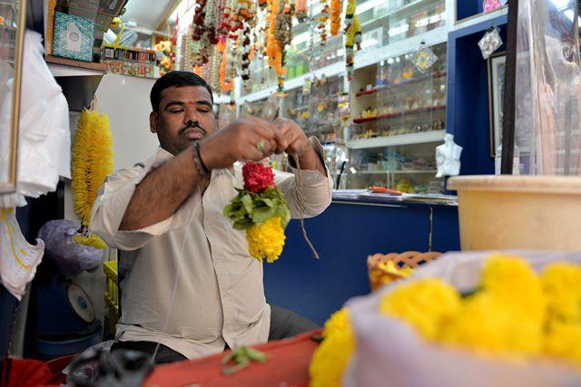 هندي يصنع قلادة من الورد تستخدم في الصلاة