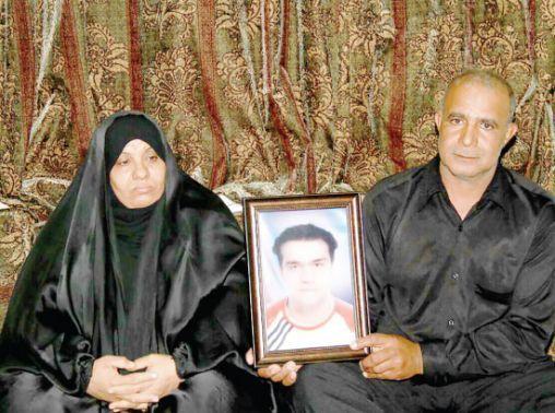 والد المسقطة جنسيته محمد<br />عبدالأمير عباس حسن يحمل<br />صورته- تصوير محمد المخرق