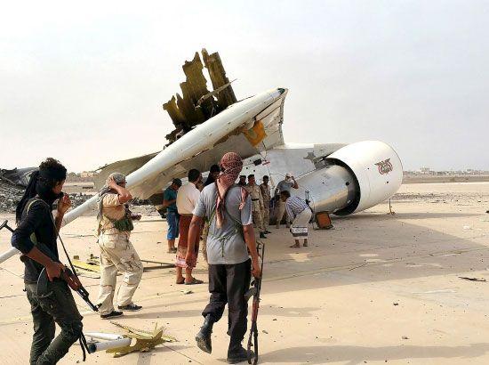 مقاتلو المقاومة اليمنية أمام حطام طائرة دمرت في مطار عدن الدولي - reuters