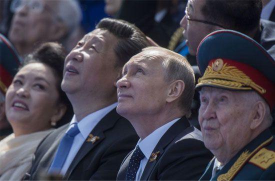 لرئيس الروسي فلاديمير بوتين والرئيس الصيني شي جين بينغ بصحبة عقيلته أثناء العرض العسكري بمناسبة الذكرى الـ70 لعيد النصر في الحرب العالمية الثانية