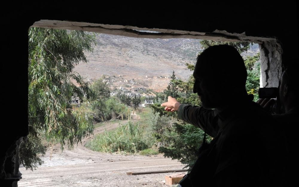 صورة صادرة عن وكالة الأنباء السورية الرسمية (سانا) تظهر جندياً سورياً يشير إلى طريق في الريف الشمالي الغربي من مدينة حماة أمس الخميس. أ ف ب