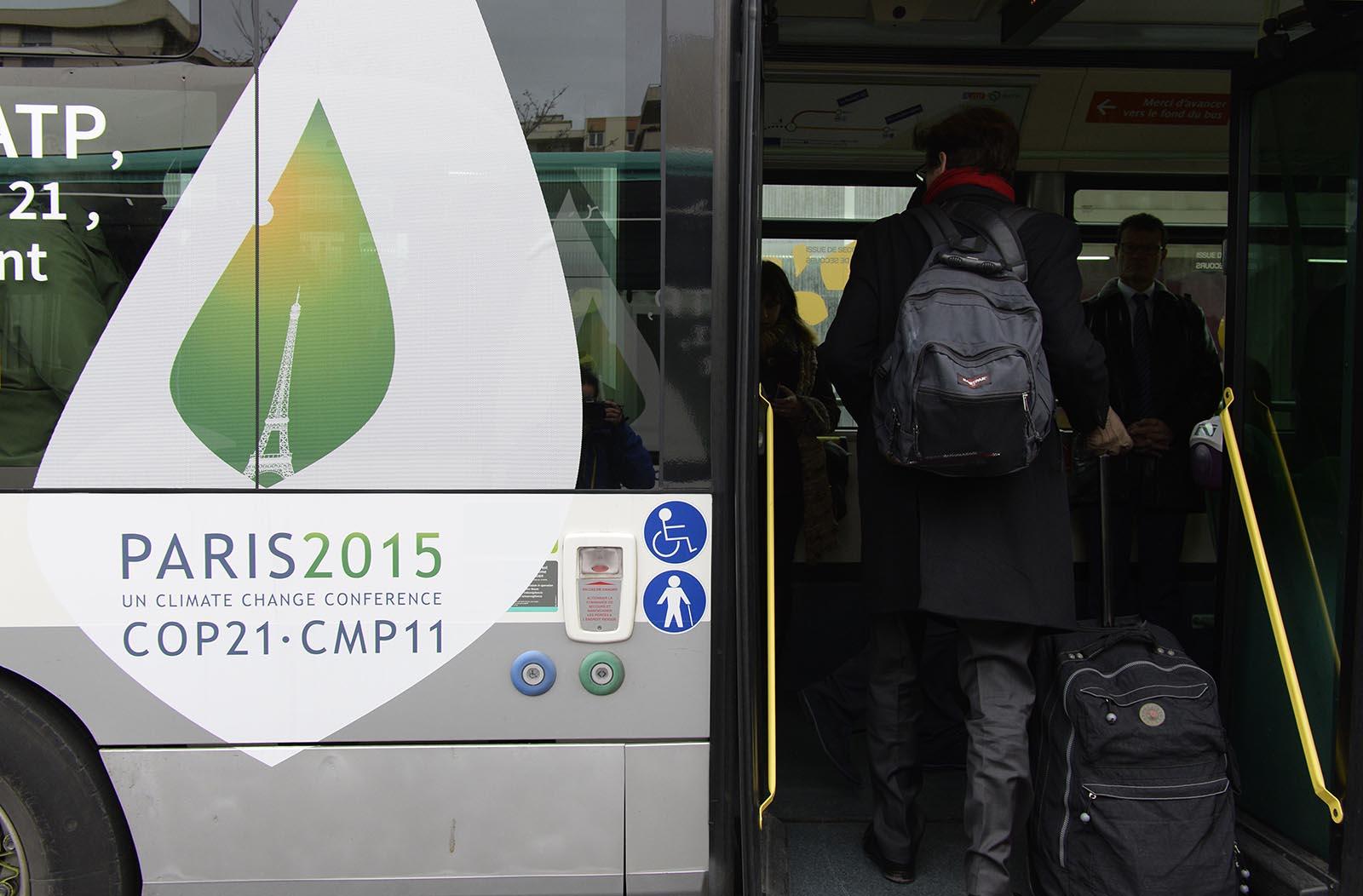 مدعون يصعدون حافلة تقلهم لمؤتمر قمة باريس للتغير المناخي COP21