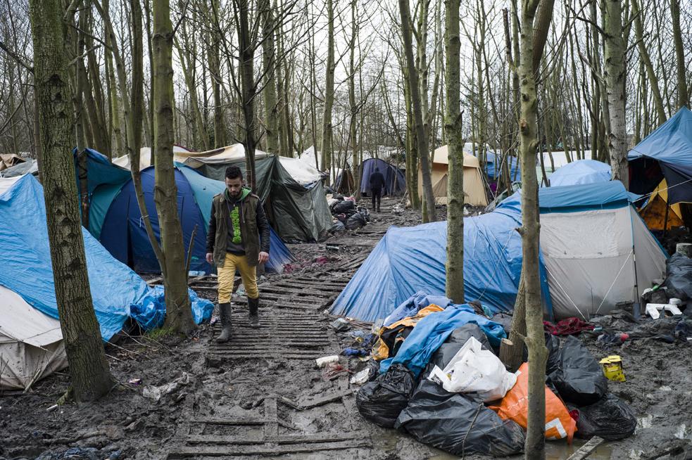 رجل يسير وسط مخيم كاليه للمهاجرين في فرنسا   (إي بي أيه)