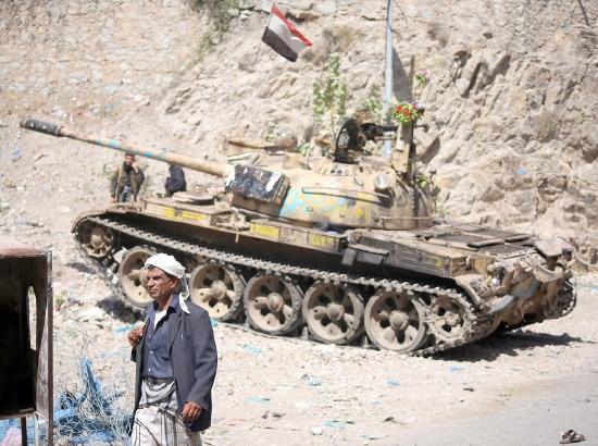 مقاتل يمني يراقب الطريق أثناء اشتباكات مع المتمردين الحوثيين غرب مدينة تعز - afp