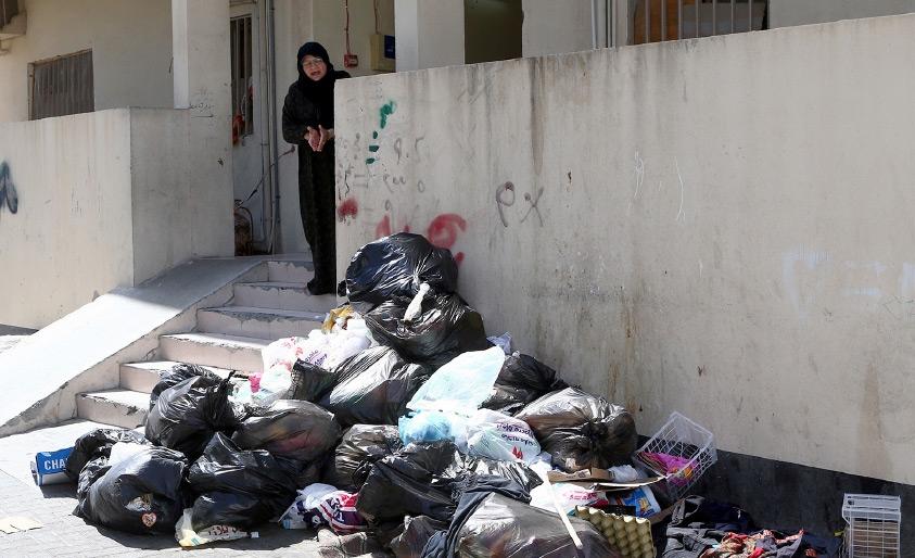 أم علي أثناء حديثها إلى «الوسط» عن القمامة المتراكمة أمام باب العمارة
