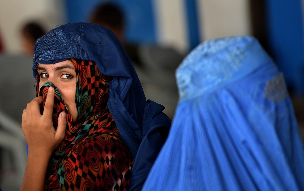 لاجئتان أفغانيتان تنتظران على متن شاحنة تابعة لمفوضية الأمم المتحدة السامية لشئون اللاجئين في بيشاور. أ ف ب