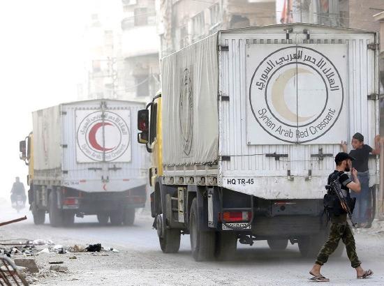 صبي سوري يسير قرب شاحنات مساعدات تابعة للهلال الأحمر شمال شرق دمشق - afp