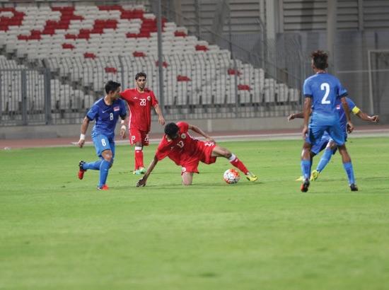 عبداللطيف يحاول مراوغة لاعبي سنغافورة