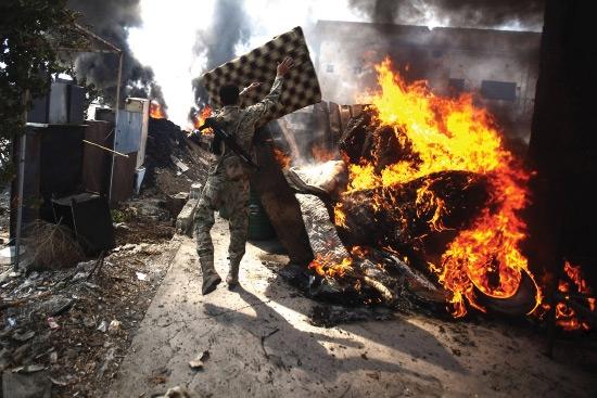 مقاتل من المتطرفين يشعل النار لرفع سحب الدخان من أجل الاختباء من القناصة في دوما  - epa