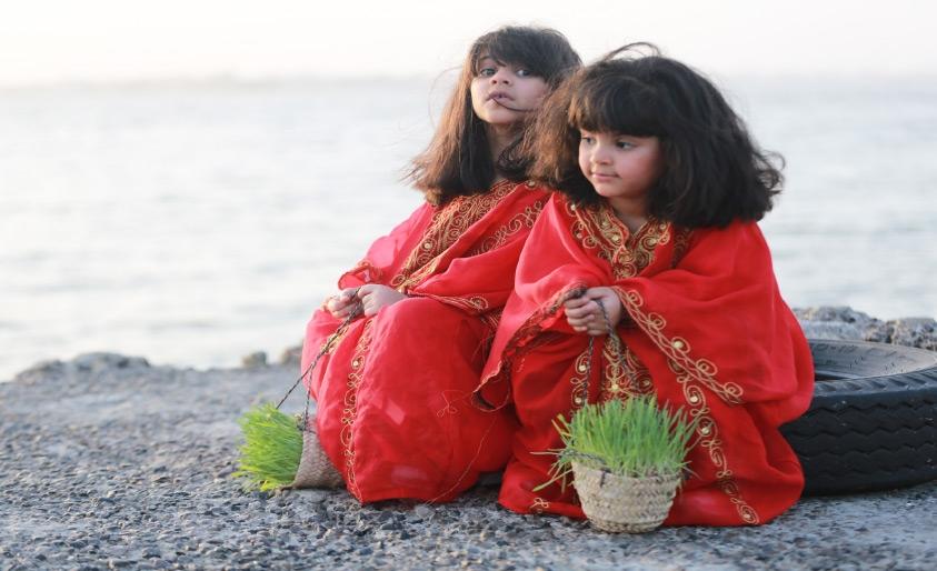 صغيرتان بالزي الشعبي تمسكان «الحية بية» على ساحل البحر