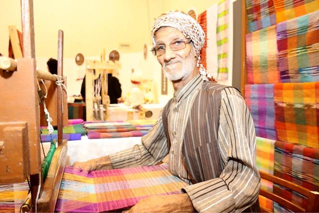أبوعصام محتضناً آلة صناعة النسيج وتظهر خلفه منسوجات حاكها بخيوط النسيج الملونة