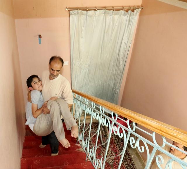 عبدالشهيد يحمل ابنه الذي لا يقوى على الحراك - تصوير : عقيل الفردان