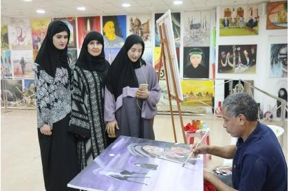 أجنبيات يرتدين العباءة خلال زيارتهن للمرسم الحسيني في المنامة - تصوير محمد المخرق