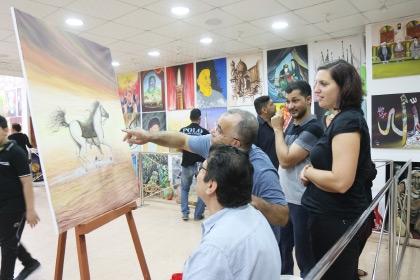 فنان بحريني يشرح لسيدة أجنبية تفاصيل لوحته في المرسم الحسيني