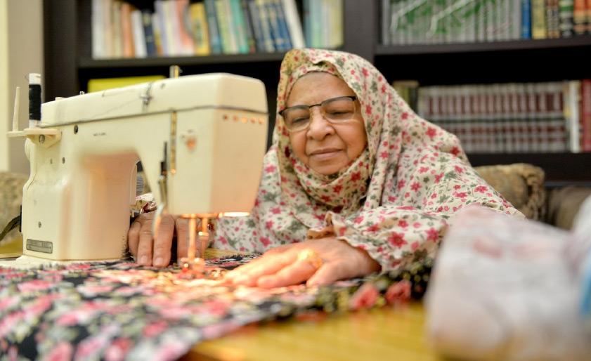أم صادق تخيط مشمرها على ماكينة «سنجر» في منزلها-تصوير احمد ال حيدر