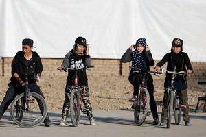 بالصور... أفغانيات يتحدين التقاليد بحركات بهلوانية على الدراجات