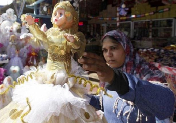 سيدة مصرية تقف بالقرب عروسة المولد الشعبية