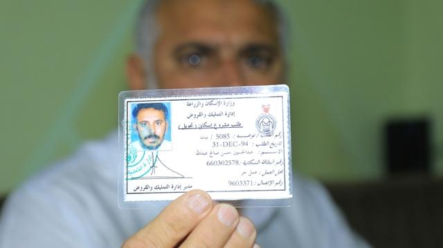 عبدالحسين يحمل بطاقة طلبه الإسكاني الذي يعود للعام 1994