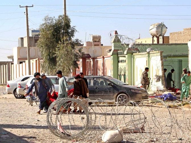 مسئولون أمنيون أفغان يحملون رفات مفجر انتحاري في موقع هجوم في لشكركاه عاصمة إقليم هلمند  - epa