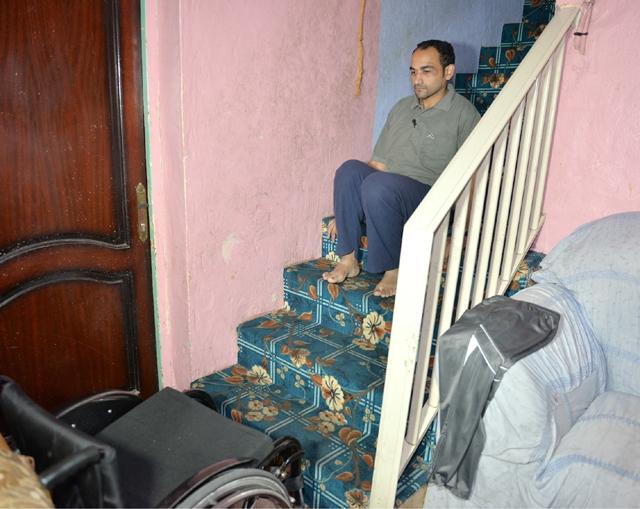 المواطن حسين سوار تجبره الإعاقة على صعود ونزول السلم وهو جالس