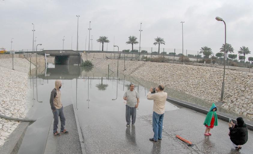 بحرينيون يلتقطون صوراً قبالة النفق الذي أغلق بفعل الأمطار