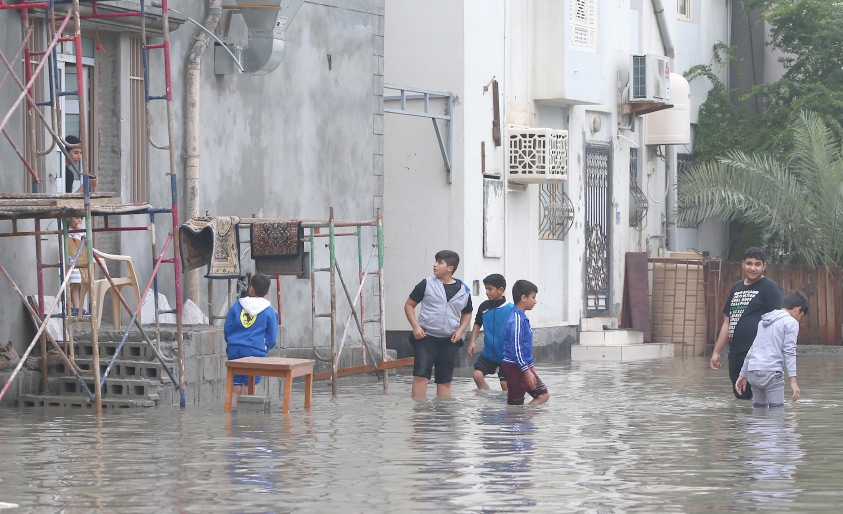 أطفال يستمتعون بمياه الأمطار التي تجمعت عند منازلهم
