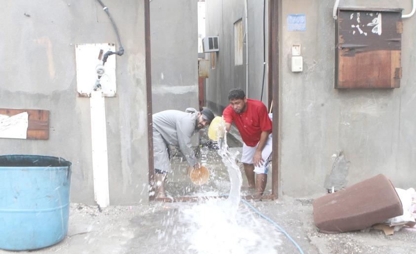 بحرينيان يشفطان المياه من داخل منزلهما