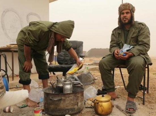 أفراد من الجيش الوطني الليبي يحتسون الشاي اثناء حراستهم لخزانات نفط في راس لانوف يوم 16 مارس اذار 2017 - رويترز
