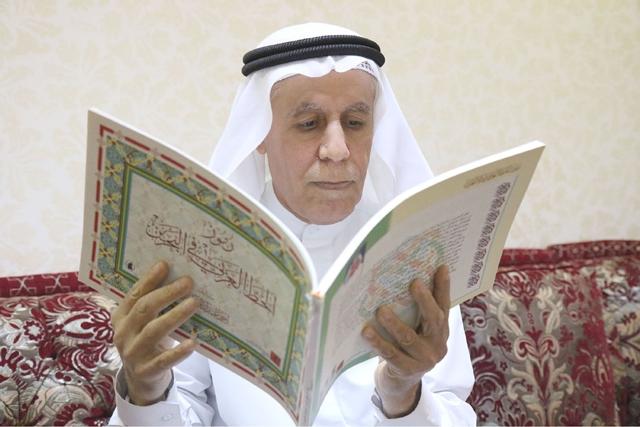 المؤلف ممسكاً بكتاب «رموز الخط العربي في البحرين»