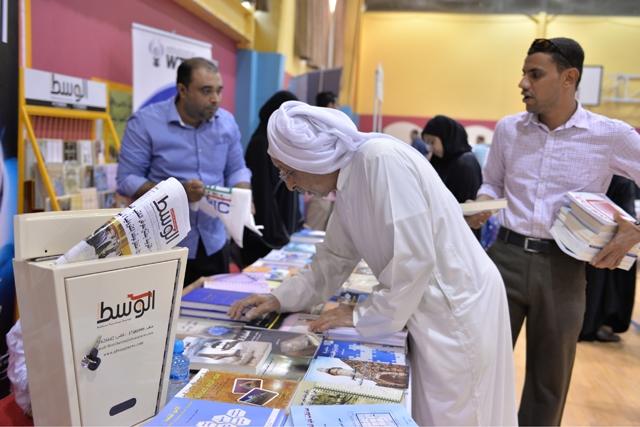 بحريني يتصفّح عناوين كتب في معرض «الوسط» للكتب المستخدمة - تصوير : أحمد آل حيدر