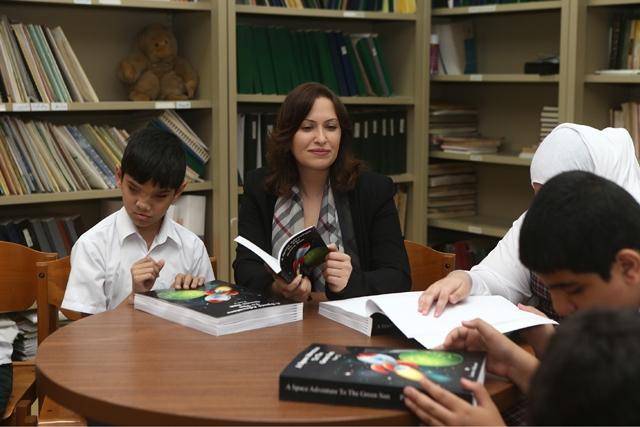 لميس الحصار تستمع لقراءة الطلبة المكفوفين أثناء الفعالية
