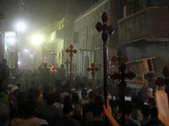 أشخاص يحملون صلبانا خشبية ويسيرون خلف جنازة مسيحيين قتلوا في المنيا يوم الجمعة  - رويترز