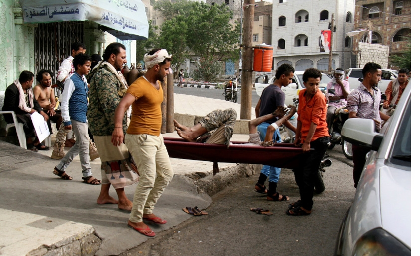 مقاتلون يمنيون يحملون مصاباً خلال اشتباكات في تعز - REUTERS
